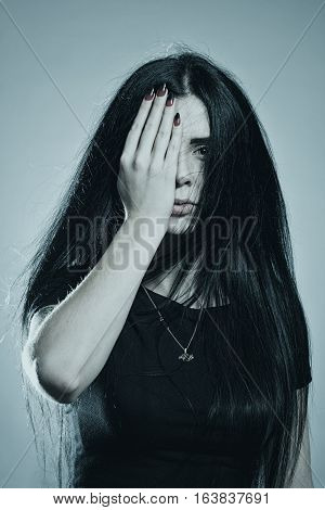 Sad serious girl holding her hand on her eyes over white background