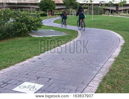 cycleway signposted a ground bikeway with two cyclists circling. Bike lane between trees in Jardin del Turia in Valencia Spain
