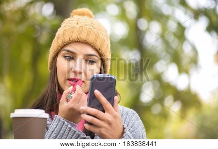 Woman making make-up applying lipstick looking at the phone like in a mirror