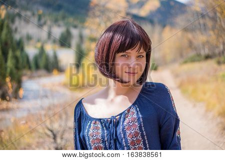 Portrait of young happy smiling woman with purple plum hair by autumn aspen trees