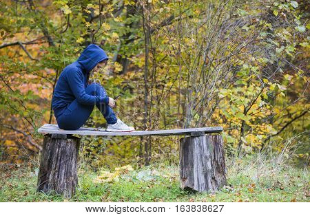 Young beautiful girl look and listening music on your mobile phone on the old bench
