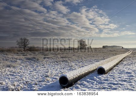 Snow-covered pipeline in a wintry landscape near Wijckel in the Dutch province Friesland
