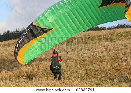 Paraglider launching his wing on a hill