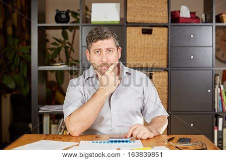Man With Calculator Pondering At Table