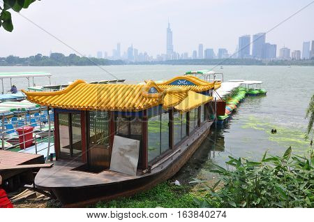 Tourism Boat at Xuanwu Lake with Nanjing skyline and Zifeng Tower at the background in Nanjing, Jiangsu Province, China.