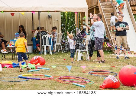 Silver Spring, USA - September 17 2016: Children playing with bubbles with machine and hula hoops at playground