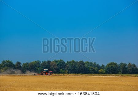 Summer day one red tractor to plow plow the soil on sloping wheat field. Agricultural land treatment before planting. The work of agricultural machinery.