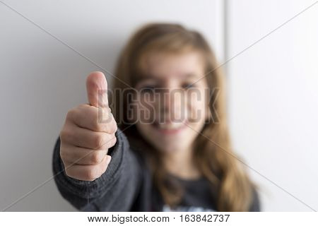 Girl with thumb up and her face out of focus