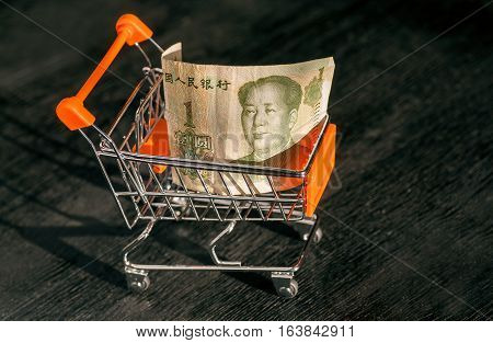 Shopping cart with a paper banknote of One Chinese Yuan and face of leader Mao, as a symbol of the modern international economy