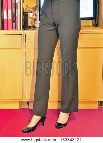 Woman wearing plain black trousers and court shoes.