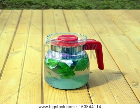 Spa tea with briar and mint in glass transparent kettle on brown wooden table against plants background