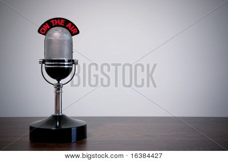 Retro microphone with an 'On the Air' illuminated sign on a desk, vignetted background.