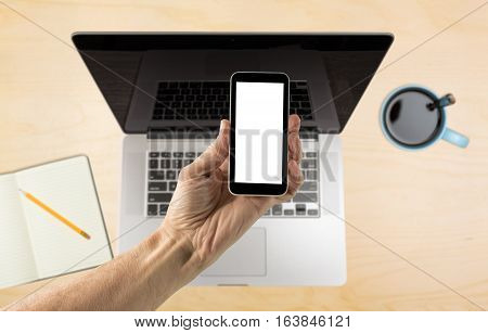Male hand holding a smartphone with a blank screen over organized desk with laptop blurred in background with copy space