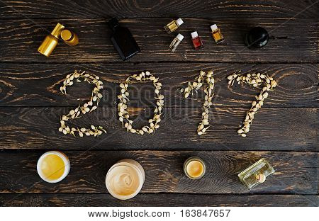Flat lay of 2017 New Year sign with jasmine flower buds. Organic spa body and skincare treatments: oil creams lip conditioner. Handmade cosmetics. Dark wooden background