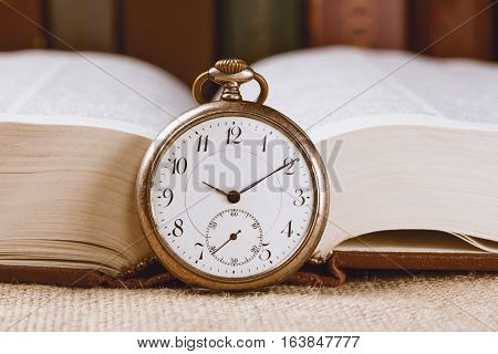 Vintage pocket clock on book against books background.