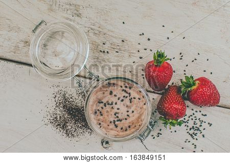 Homemade yogurt in a jar with strawberry seeds and cacao. Dessert with strawberries on a white wooden background. Fresh juicy strawberry with yogurt. Directly above. Top view. Horizontal.