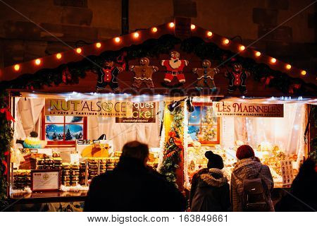 STRASBOURG FRANCE - DEC 20 2016: Christmas Market stall selling traditional Alsatian nut creme and traditional French cuisine with customers admiring the large selection of food
