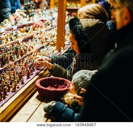 STRASBOURG FRANCE - DEC 20 2016: Kids buying traditional Christmas hand-made toys figurines of cinema and religious characters at the oldest Christmas Market in Europe Strasbourg