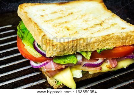 grilled sandwich or panini on grill with bacon cheese onion salad and tomatoes. selective focus