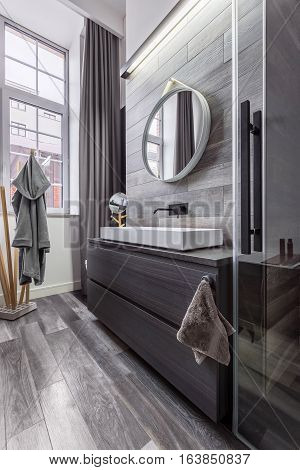 Wooden Bathroom With Round Mirror