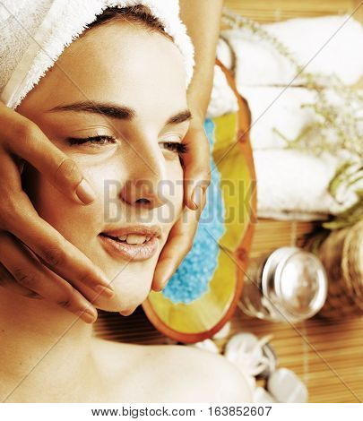 stock photo attractive lady getting spa treatment in salon, close up asian tan manicured hands on face