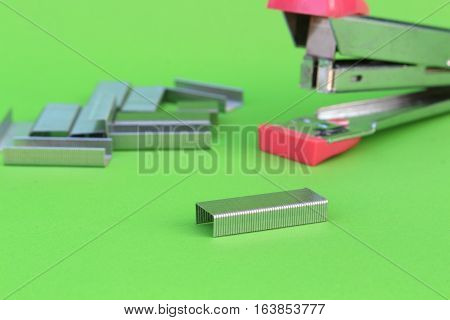 close up staples on isolated green background