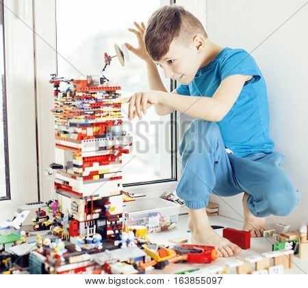 little cute preschooler boy playing lego toys at home happy smiling, lifestyle children concept close up