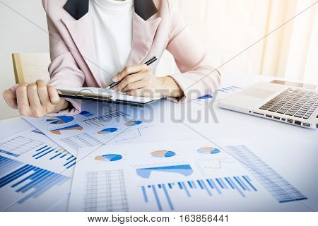Portrait Of Business Woman With Laptop, Finance Graph And Writes On A Document At Her Office