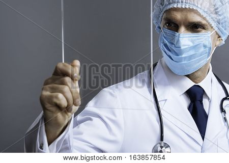 Do it properly. Handsome confident smart doctor in face mask looking through medical glass and wearing surgical scrub cap while posing on a grey background.