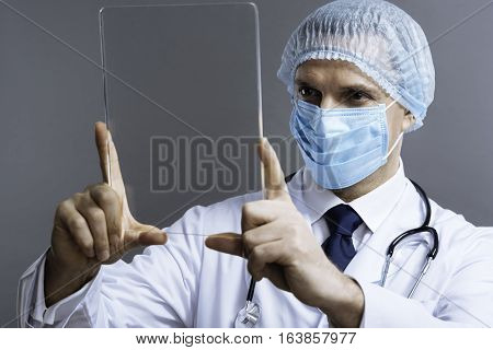 My lovely job. Handsome confident delighted doctor in face mask posing with medical glass and wearing surgical scrub cap while standing on a grey background.