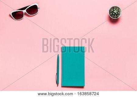Creative flat lay photo of workspace desk with aquamarine notebook, eyeglasses, cactus copy space pink background, minimal style.
