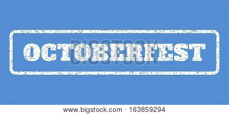 White rubber seal stamp with Octoberfest text. Vector message inside rounded rectangular frame. Grunge design and dirty texture for watermark labels. Horisontal sign on a blue background.