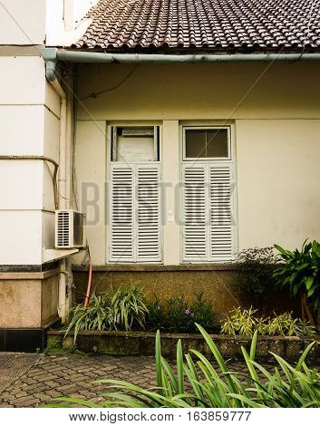 One side of a house with bushes photo taken in Semarang Indonesia java