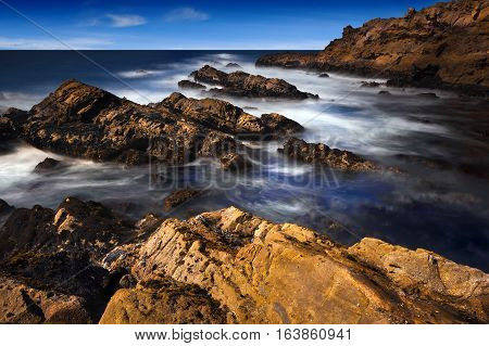 California Coast with ocean waves and rock formations.