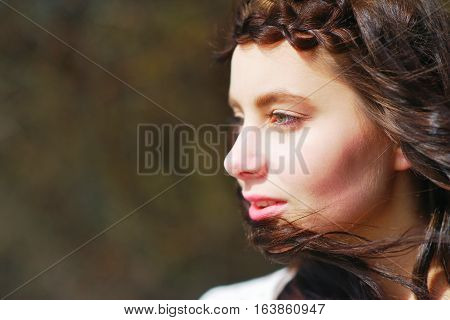 Portrait of a dreamy beautiful woman with silky hair beautifully plaited in a pigtail and fluttering in the wind outdoors with a blur effect on a dark background closeup