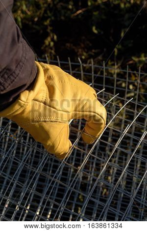 Male Yellow Gloved Hand Handling Chicken Wire