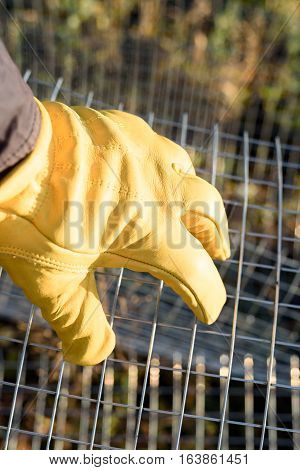 Yellow gloved male hand grasping metal chicken wire poster