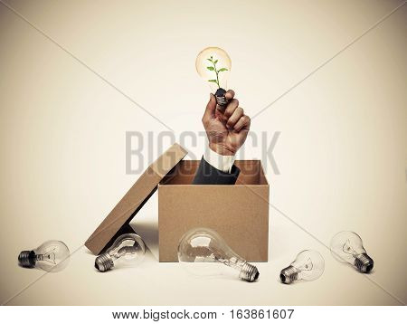 Hand of a businessman holding a light bulb with a tree coming out from a brown paper box surrounded by old incandescent light bulbs / Change to green energy concept