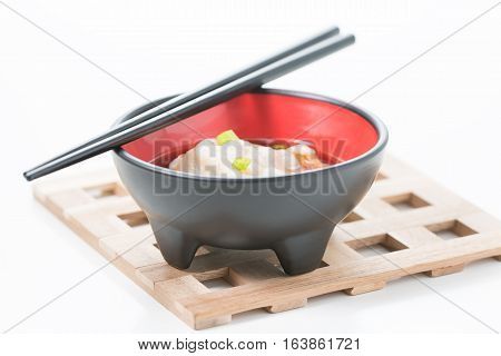 Wonton soup served in a black bowl on a wooden trivet.