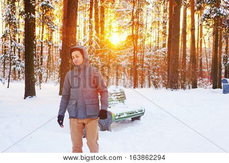 Young smiling man walks in beautiful winter Park during sunset.