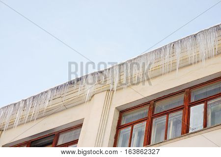 Big transparent icicle hanging from the roof of a building on a clear frosty day.
