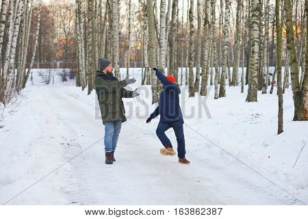 Two young men on a walk in winter Park. One of them slipped and lost his balance waving his arms falls back his friend wants to support it.