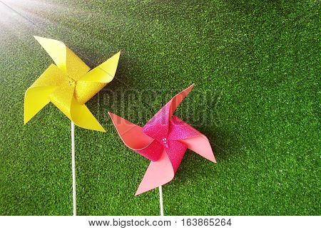 Pink and yellow pinwheels on the artificial grass background. Picture with copy space.Artificial light was added on the top left corner.