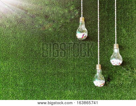 Three lamp-shaped bottles on artificial green grass background. Artificial light was added on the top left corner. Picture with copy space