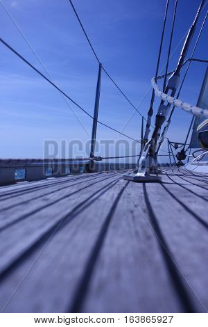The Curved Teak Deck Of A Yacht Sailing At Sea