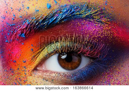 Close up view of female eye with bright multicolored fashion makeup. Holi indian color festival inspired. Studio macro shot