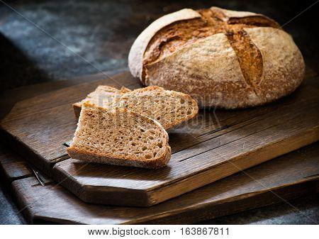 Homemade sliced rye artisan sourdough bread over dark background selecrive focus closeup