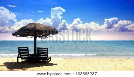 Beach chairs on the tropical sand with cloudy blue sky