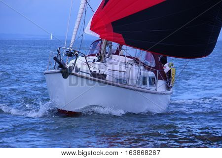 yacht sailing with a red and black spinnaker on the solent