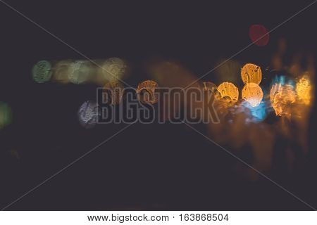 Frozen window with Blurred Defocused light of Night City abstract background